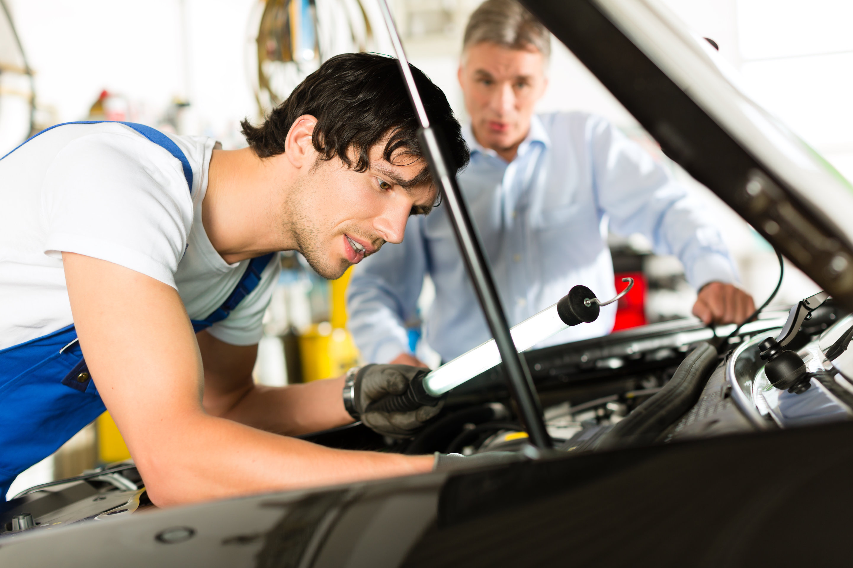 Mature client and young mechanic looking under car hood at engine with lamp